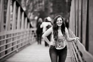 black and white of fun senior girl laughing on bridge